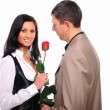 Young man gives his girlfriend a rose — Stock Photo