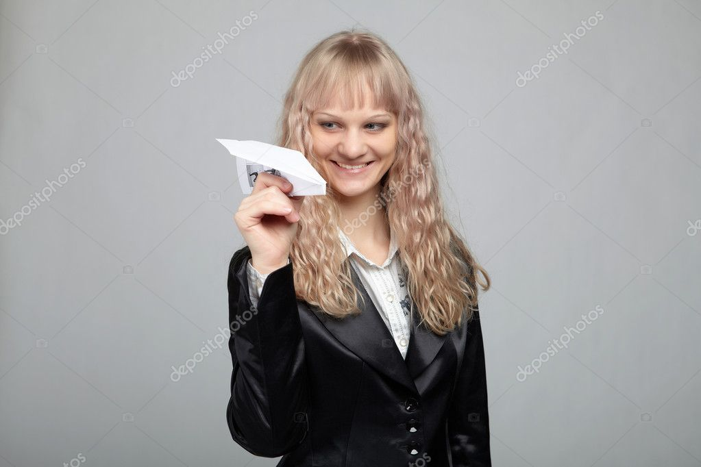 Funny business woman in a black suit with a gray background runs out of paper airplanes — Stock Photo #4550054
