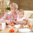 Grandmother feeding granddaughter at home — Stock Photo