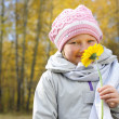 Little girl with a yellow flower - Stock Photo