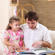 Stock Photo: Young father reading a book to his daughter
