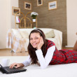 A young girl with a lap top at home - ストック写真