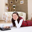 A young girl with a lap top at home - Stok fotoğraf