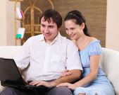 Junge Familie zu Hause mit einem laptop — Stockfoto