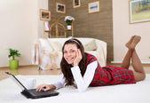Una chica joven con un ordenador portátil en casa — Foto de Stock