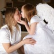 Stock Photo: Girl dressed as an angel kissing her mother