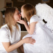 Girl dressed as an angel kissing her mother - Stock Photo