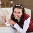 A young girl with a mug top at home - Stockfoto