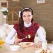Young girl eating healthy food at home — ストック写真