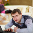 Young man with a laptop at home — Stock Photo