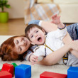 Stock Photo: Young mother playing with her little son
