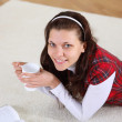 A young girl with a mug top at home — Stock Photo