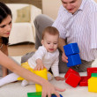 Young family at home playing with a baby — Stockfoto