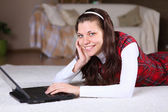 Uma jovem garota com um lap top em casa — Foto Stock