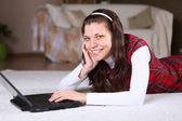 Una giovane ragazza con un lap top a casa — Foto Stock