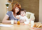 Mother feeding a baby at home — Stock Photo