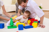 Young family at home playing with a baby — Stock Photo