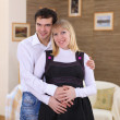 Pregnant wife and her husband at home - Stok fotoğraf