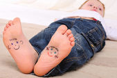 Small faces painted on the soles — Stock Photo