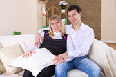Young couple at home on a sofa — Stock Photo