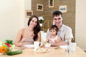 Família de jovem em casa a comer — Fotografia Stock