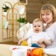 Mother feeding her little son at home — Stock Photo