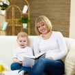 Little boy and his mother at home reading a book — Stock Photo