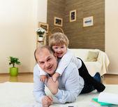 Padre e hijo jugando en el piso en casa — Foto de Stock