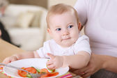 A young mother feeding her baby at home — Stock Photo