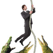 Business man climbing up from crocodiles — Stock Photo