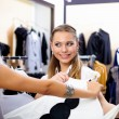 Young woman in a shop buying clothes — Stock Photo #5157051