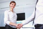 Handshake by a business woman — Stock Photo