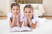 Twin sisters together at home with books — Stock Photo
