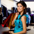 Young woman in a shop buying clothes — Foto de Stock