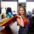 Young woman in a shop buying clothes - Stock Photo