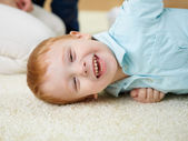 Feliz sorrindo e rindo do menino em casa — Foto Stock