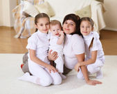 A young mother with her three daughters at home — Stock Photo