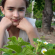 Stock Photo: Girl and strawberry bush at garden