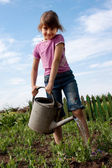Little girl with watering can — Stock Photo
