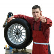 Handsome  young car mechanic with wheel - Foto Stock