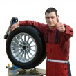 Handsome  young car mechanic with wheel - Zdjęcie stockowe