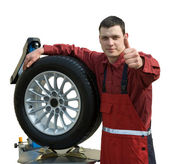Handsome young car mechanic with wheel — Stock Photo