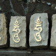 Four stones with sacred tibetan buddhist syllable — Stock Photo