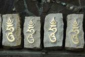 Four stones with sacred tibetan buddhist syllable — Stock Photo