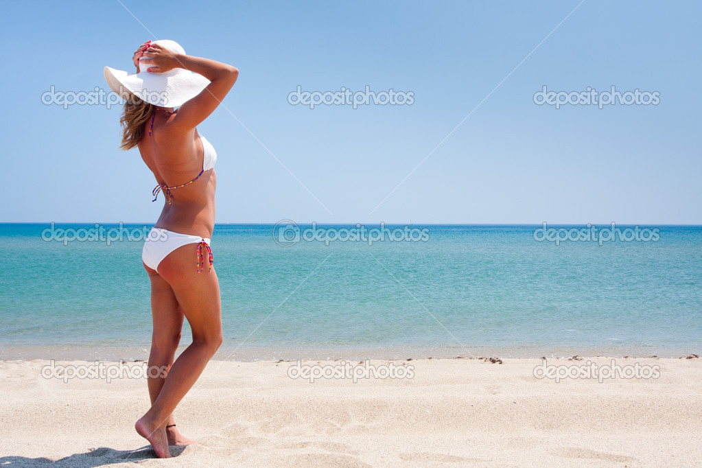 Young woman standing on a beach and enjoying the sun — Stock Photo #3494380
