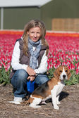 Girl with her dog on flower field — Stock Photo
