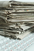 Newspapers on keyboard — Stock Photo