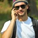 hombre sonriendo y hablando por un teléfono móvil — Foto de Stock