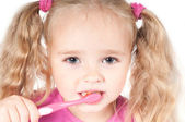 Little cute girl in studio brushing teeth — Stock Photo