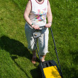 A woman with an electric mower at the cottage — Stock Photo